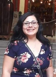 Photo of A woman with dark hair wearing glasses and a flower print blouse smiling.